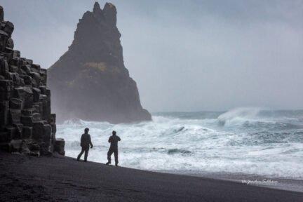 Zwei Personen am Strand von Reynisfiara in Island