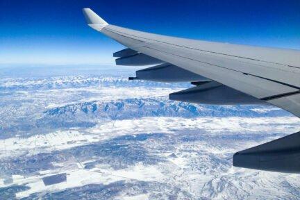 Flugzeugflügel über verschneiter Landschaft
