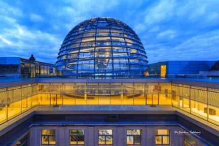 Kuppel des Bundestags in Berlin mit darunter gelegenem Stockwerk zu blauer Stunde