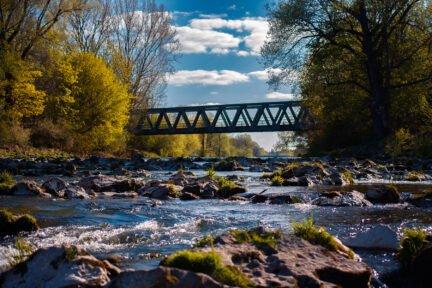 Eine Eisenbrücke über einen Fluss mit Steinen darin und mit Bäumen links und rechts
